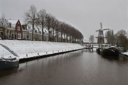 rampage: View on city canal to houses and classical windmill in snow. A row of trees stands between the historical houses and the canal. There are a few boats lying in the water. You can see a bridge as well