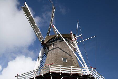 exceeding: Campana Reed o molino de viento cl�sico contra el cielo azul con nubes Foto de archivo