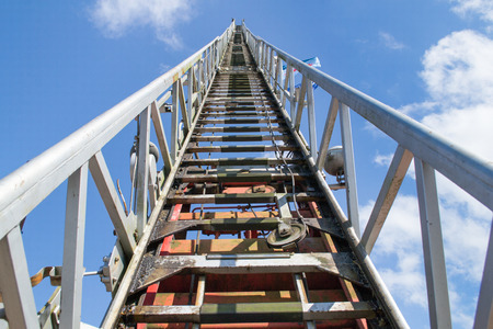 Stairway to heaven: Fire brigade ladder into a blue sky with white clouds photo