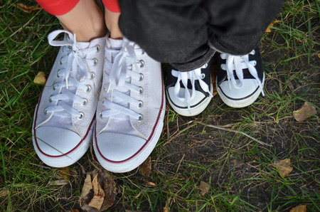 foots: Mom and son legs on the grass in the sneakers Stock Photo