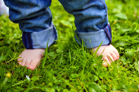 foots: Small baby foots on the green grass Stock Photo