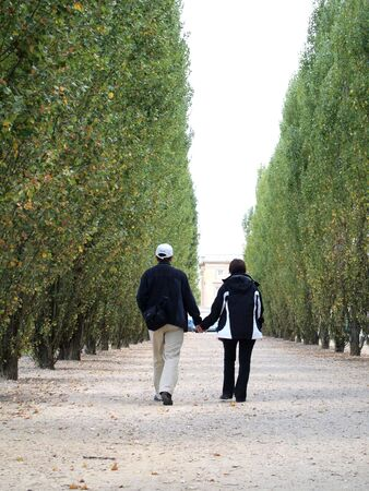 Couple walking together on the walk way to Marie Antoinettes Cottage at Versailles in France  photo