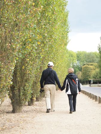 Couple Holding Hand and Walk together at Versailles in France photo