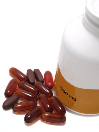Nutritional supplement pills in white background and shallow depth of field. The yellow Gell are Lecitine and brown pill are Vitamin E with White pill bottle photo