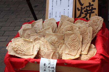 Taiyaki is a Japanese fish-shaped cake. The most common filling is red bean paste that is made from sweetened azuki beans. photo