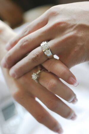 ring wedding: Wedding rings on hands of bride and groom, focus on rings of man Stock Photo