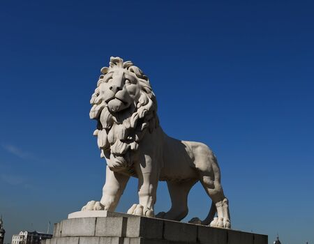 river bank: Imposing lion statue guarding the south bank of the Thames River near the London Eye ferris wheel attraction in London  Stock Photo