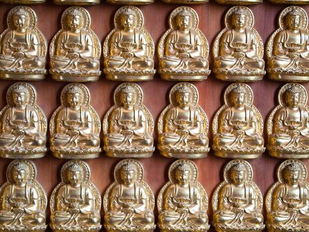 Many small Buddha statue on the wall at chinese temple in Thailand  photo
