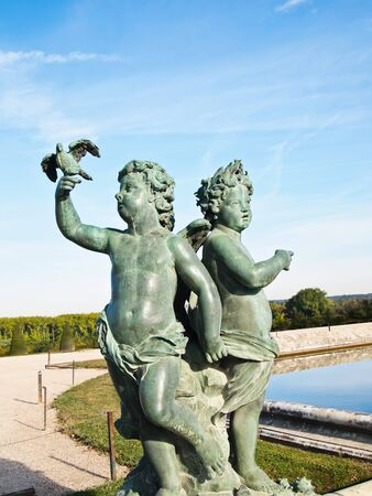 Both Baby and Pigeon Statue at Versailles castle in France