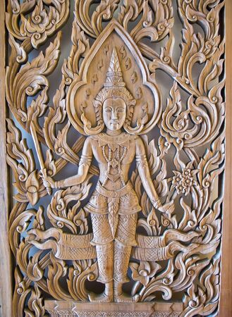 A Deva statue , wood door at Wat Saket temple in Bangkok , Thailand