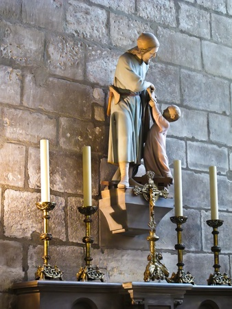 Statue of a saint and boy inside Notre Dame Cathedral in Paris, France.