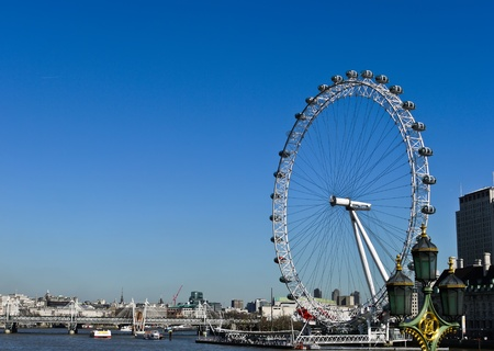 The London Eye and River Thames with blue sky on the background in London , UK