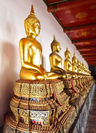 A row of seated Buddhas statue at the temple of Wat Pho in Bangkok, Thailand (Vertical) photo
