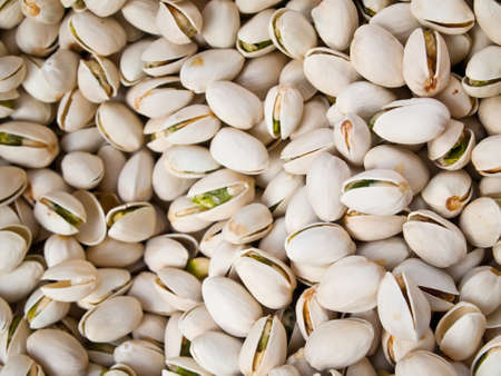 background of roasted pistachio nuts in their shells photo