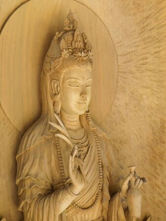 Kuan Yin image of buddha , Wood carving in a thai temple. Foto de archivo