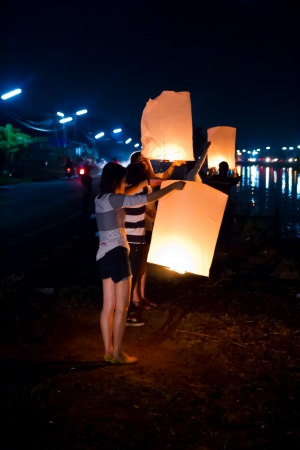 CHONBURI, THAILAND - NOVEMBER 28: Two people holding a flying fire lantern to celebrate the Loy Krathong festival. November 28, 2012 in Hua Hin, Thailand. Stock Photo - 17002975
