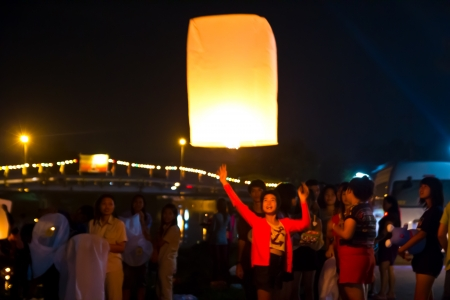 CHONBURI, THAILAND - NOVEMBER 28: Two people holding a flying fire lantern to celebrate the Loy Krathong festival. November 28, 2012 in Hua Hin, Thailand. Stock Photo - 17002993