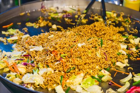 Close up of stir-fry noodles in wok pan photo