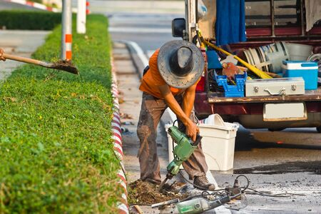 Road worker on a sidewalk with a jackhammer digging up concrete photo