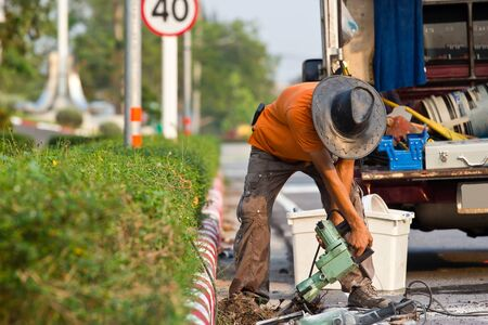 noise pollution: Road worker on a sidewalk with a jackhammer digging up concrete