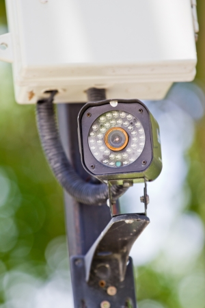 Security camera on the post with outdoor housing photo