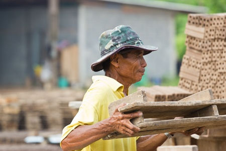 laborer: man laborer lifts the wood of Production of bricks in thailand