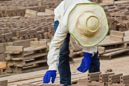 bloc: Woman laborer is dislocating a brick of Production of bricks in thailand