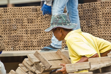bloc: Man laborer lifts the wood of Production of bricks in thailand Stock Photo