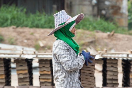 bloc: Woman laborer lifts the wood of Production of bricks in thailand