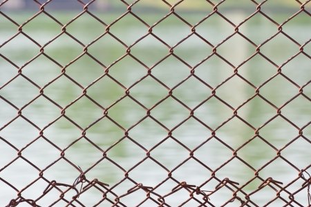 Metal mesh wire fence with blur water background photo