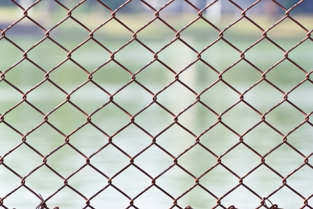 chained link: Metal mesh wire fence with blur water background Stock Photo