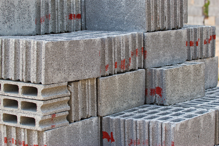 masonary: gray concrete construction blocks (breeze block, cement block, foundation block, besser block; pro term: Concrete Masonary Unit - CMU) in a straight stack Stock Photo