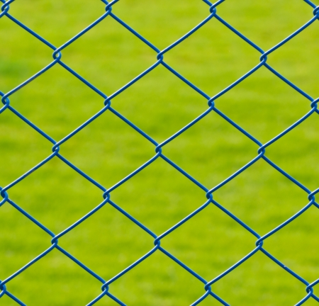Metal mesh wire fence with grass background