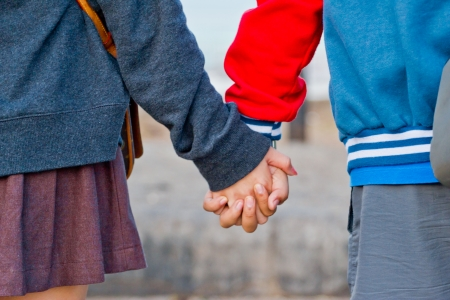 Young beautiful stylish couple in love holding hands photo