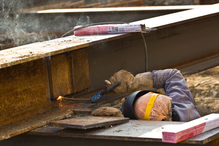 erecting: outdoor worker with protective mask welding metal and sparks