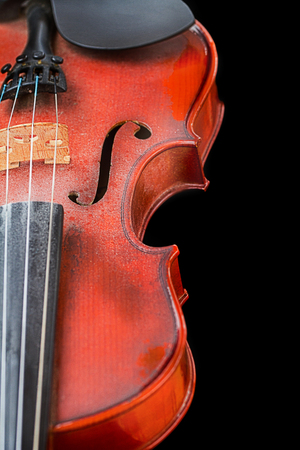 Close up of shiny violin on wooden table, isolated on black background, with clipping path photo