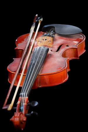 Close up of shiny violin on wooden table, isolated on black background, photo