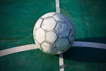 Old used football or soccer ball on cracked asphalt photo