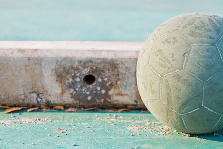 raged: Old used football or soccer ball on cracked asphalt