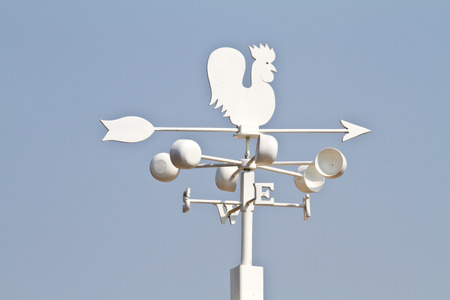 blustery: Weather vane - cockerel which reflected sun against bright-dark blue sky Stock Photo