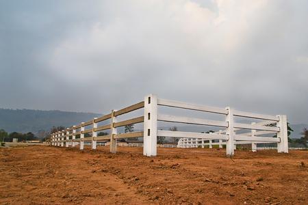 cerca blanca: valla de blanco en el campo agr�cola y cielo nublado
