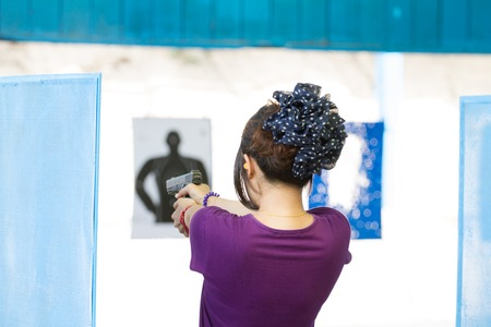 Target practicing with gun In the shooting range photo