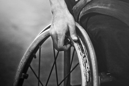 Close-up of male hand on wheel of wheelchair during walk