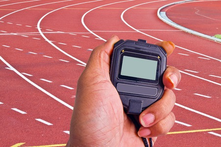 Close-up of  man holding  stopwatch to measure performances of the  photo