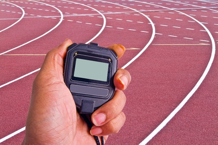 Close-up of  man holding  stopwatch to measure performances of the runners in a stadium photo