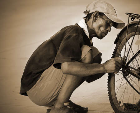man old repair a bicycle photo