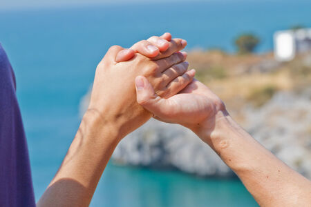 Man and woman hands touch in gentle, soft way on blue sunny sky  Concepts of connection, hope, faith, help, love