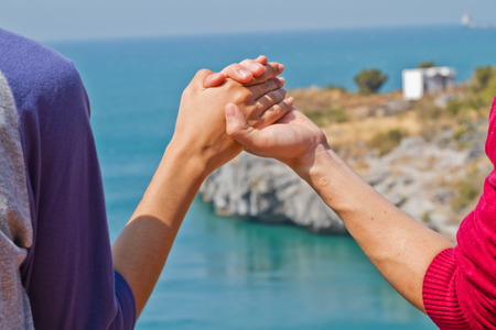 Man and woman hands touch in gentle, soft way on blue sunny sky  Concepts of connection, hope, faith, help, love  photo