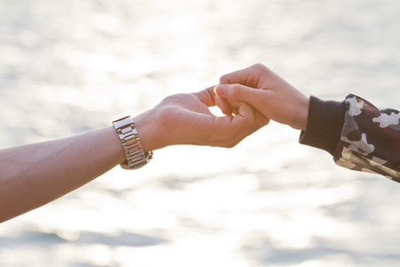Young couple in love  holding hands looking in the sunset photo