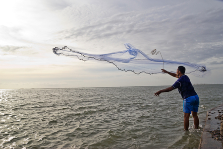 throwing fishing net at thai sea photo